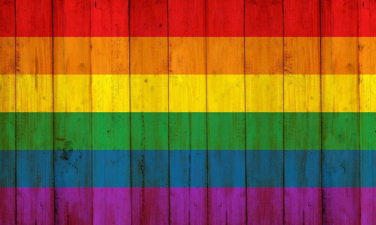 Gay flag rainbow on wooden fence texture
